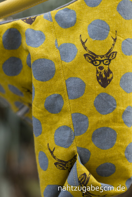 Seitenansicht der zweiten Arya Handtasche. Currygelber Stoff mit grau-blauen unregelmäßigen Punkten und Hirschen mit Brillen.